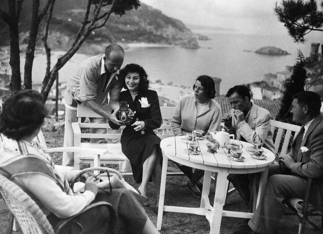November 1956, Costa Brava, Spain --- 11/1956-Costa Brava, Spain: When Frank Sinatra heard of romance brewing between Ava Gardner and Mario Cabre in 1950, he rushed over to Spain with a bagful of jewels to woo Ava back.  Here they are sitting in a garden overlooking the beautiful Costa Brava.  Sinatra, second from right, chain smokes... --- Image by © Bettmann/CORBIS